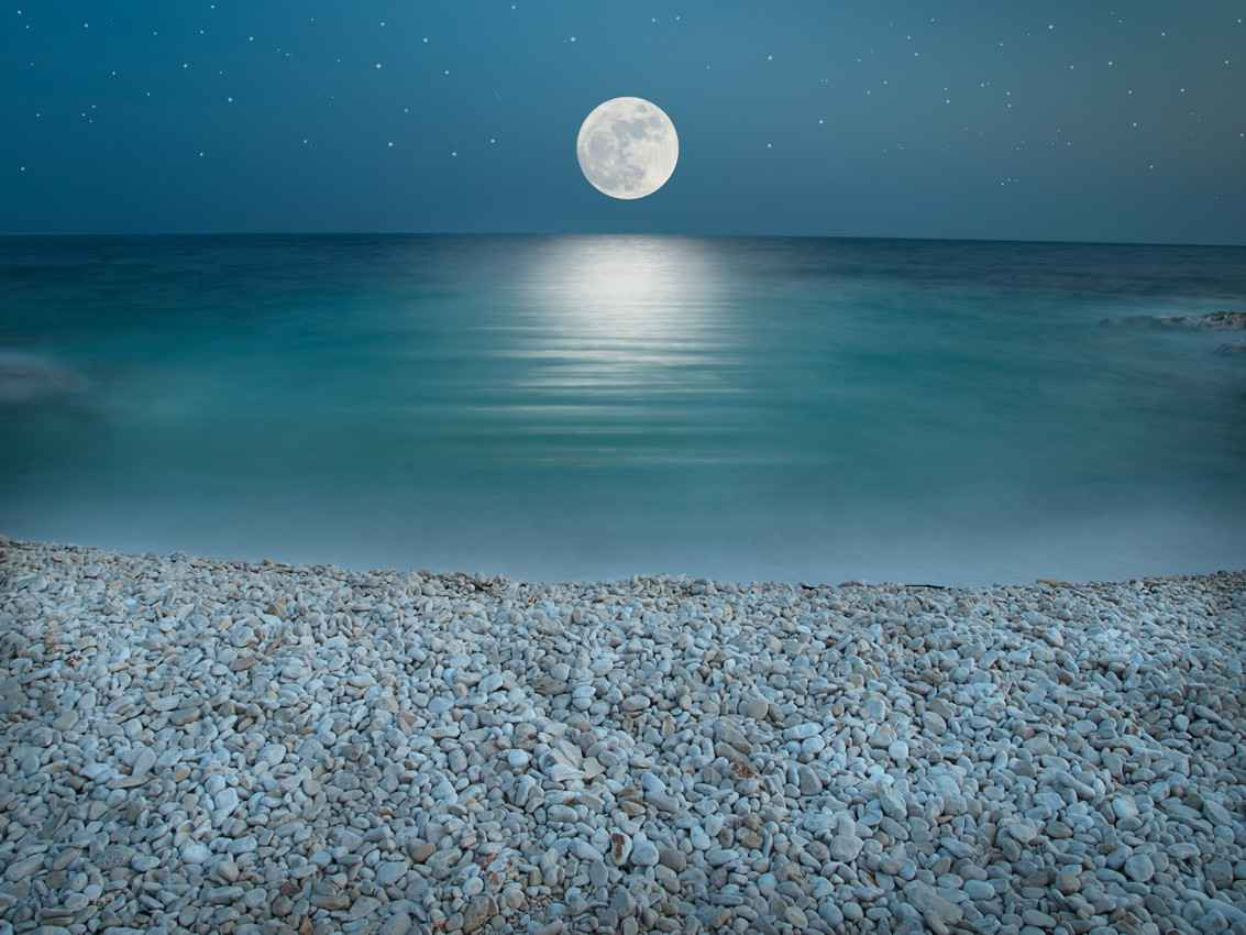 A full moon shining over the Caribbean Sea.
