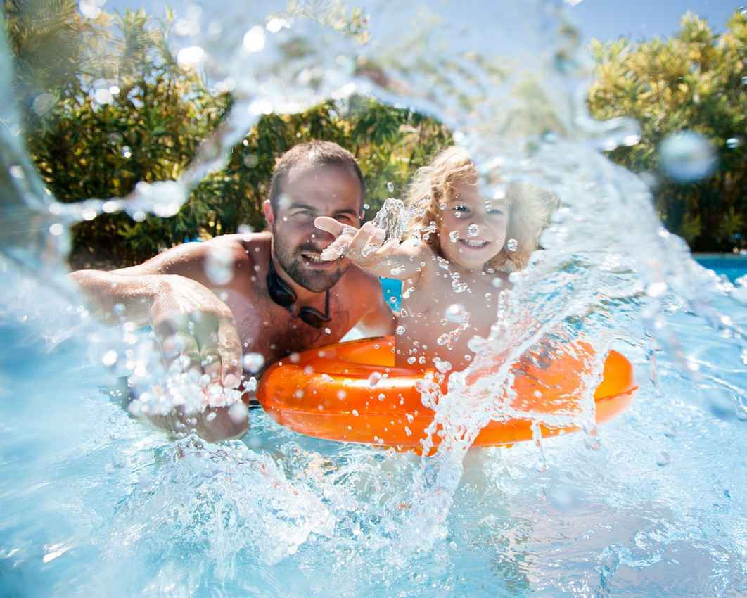 A father and a daughter playing in a swimming pool.
