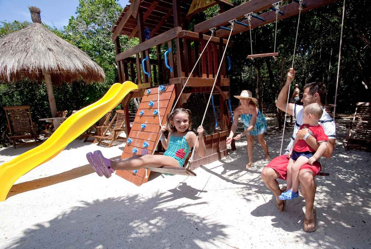 A mother and father with two children playing at a Playa Del Carmen family resort jungle gym.