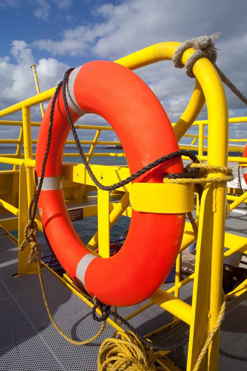 A lifesaver strapped to the side of a ferry boat rail.
