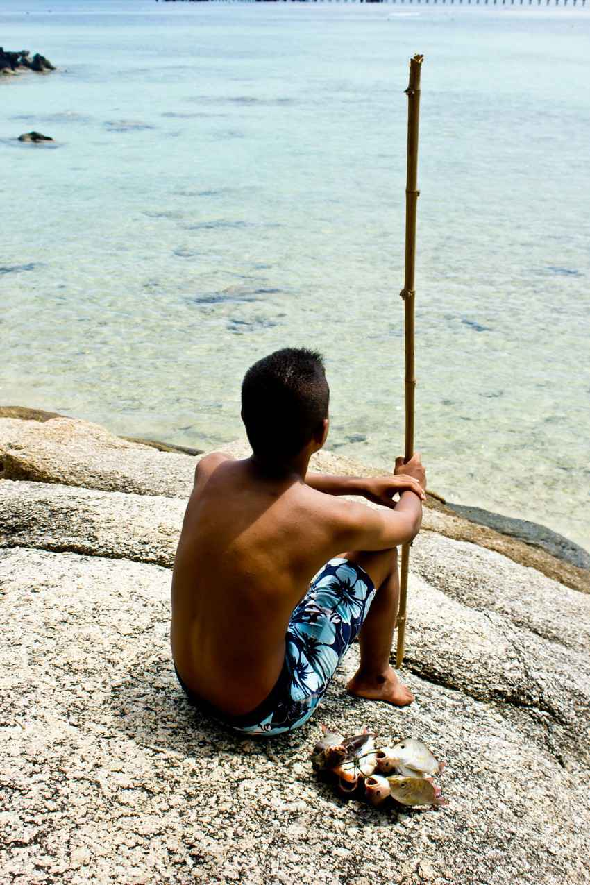 A young local boy was fishing with a fishing pole made from a stick.