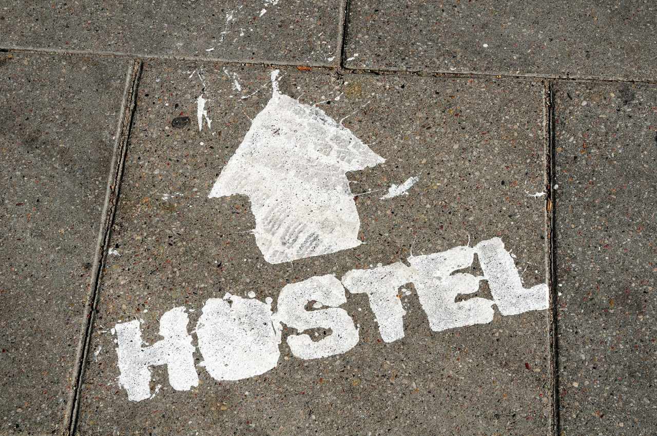 Hostel written in paint on a cement sidewalk.