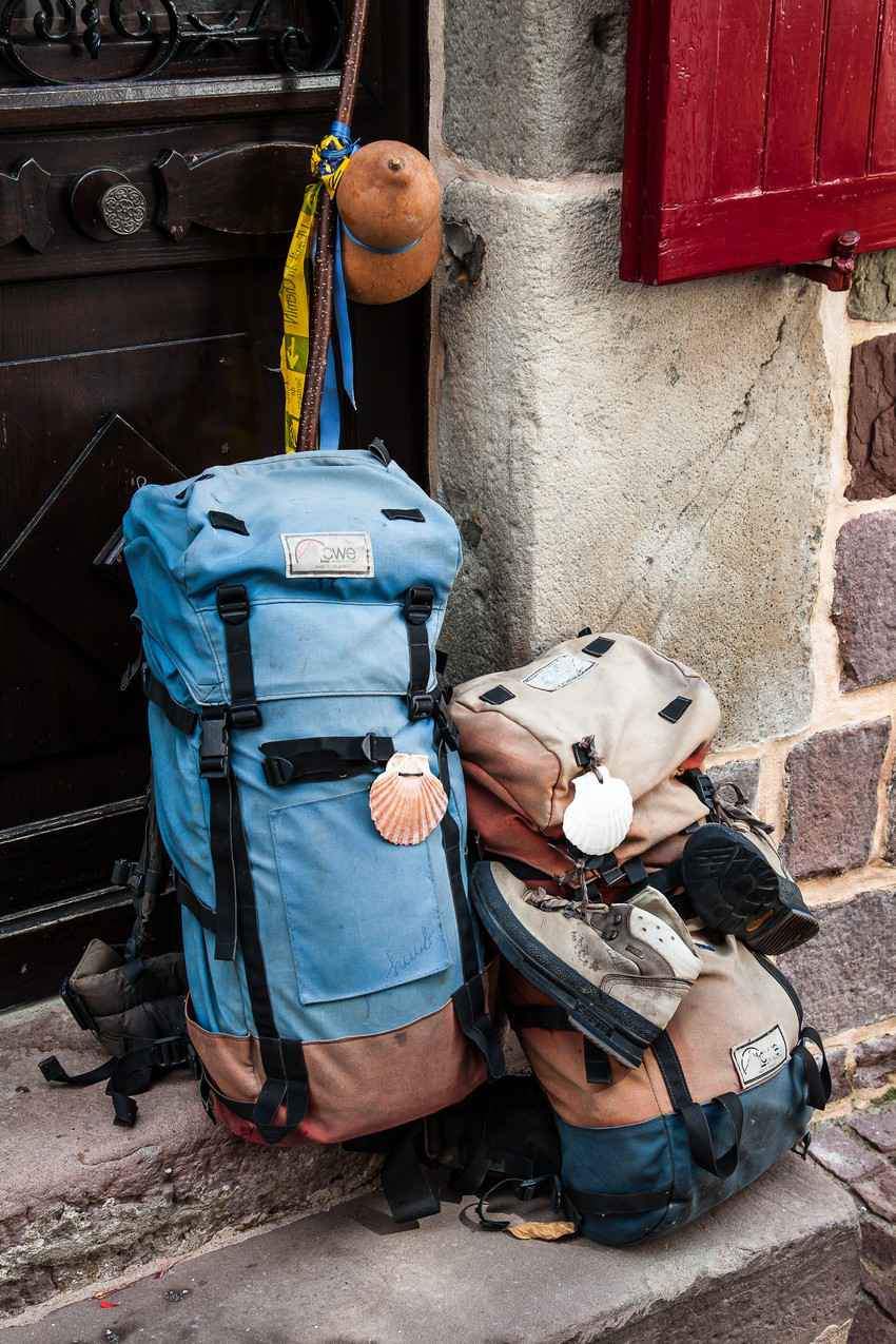 Several backpacks on a street entrance.