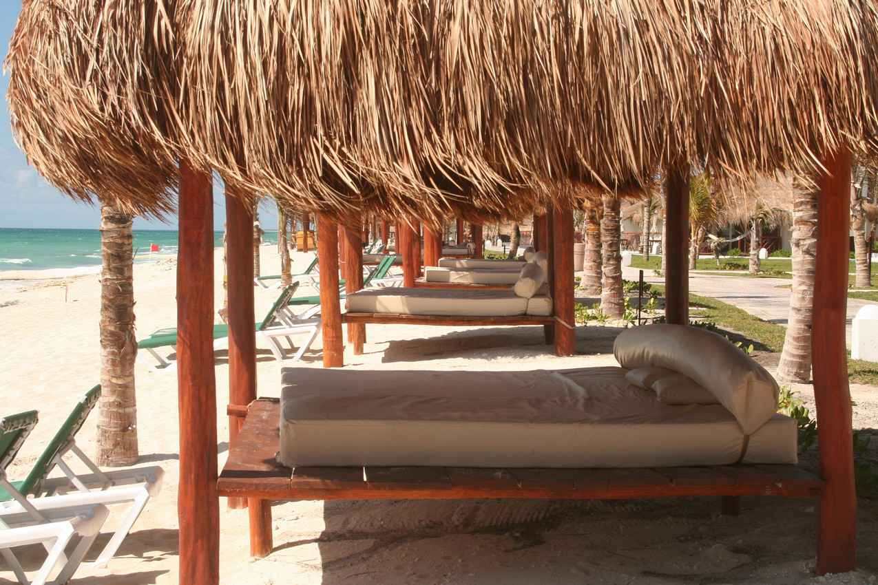 A row of parental beds with palapas overhead on the beach in Playa Del Carmen.