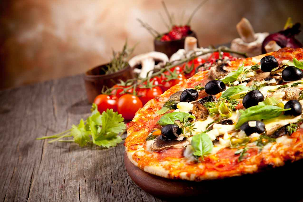 An Italian style pizza with mushrooms, olives, tomatoes, and other herbs.