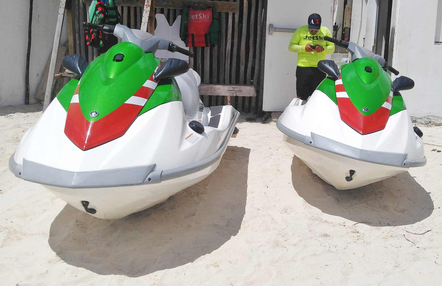 Picture taken of front view of two green and white jet skis on the beach in Playa Del Carmen, Mexico.