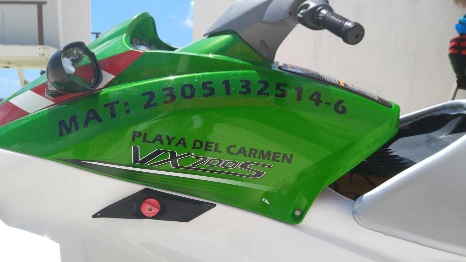 A jet ski that displays a license number and the words Playa Del Carmen written on the side.