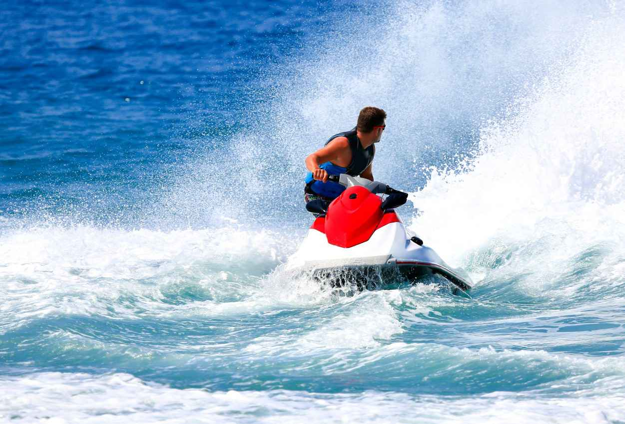 A man looking backwards while riding a jet ski.