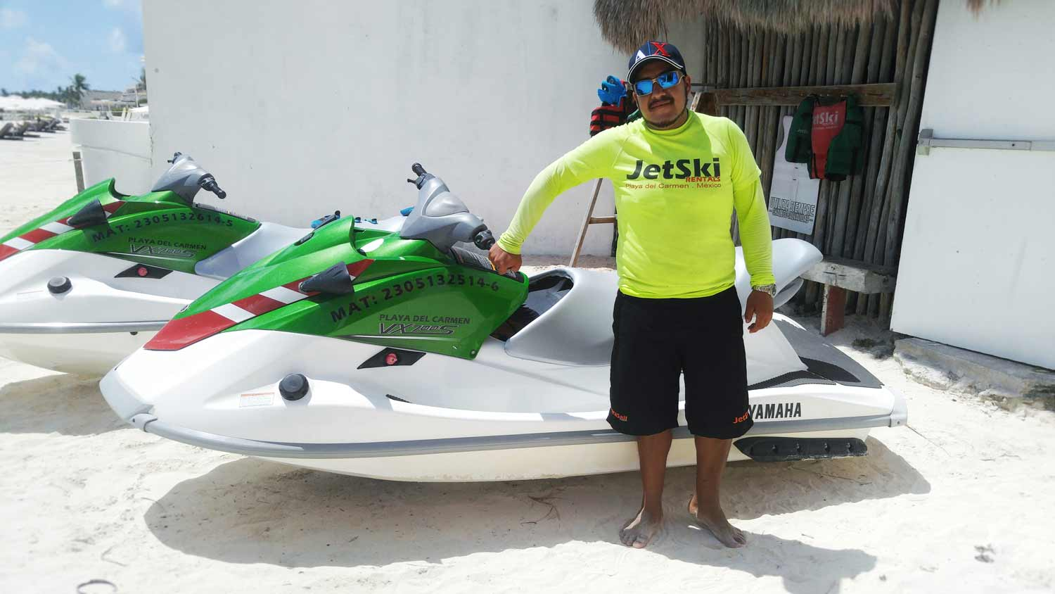 Oscar, one of the people who works at the jet ski rental area, standing next to a wave runner in Playa Del Carmen.