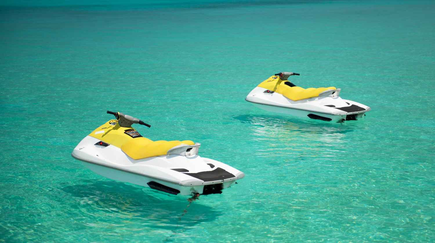 Two jet skis in crystal clear water.