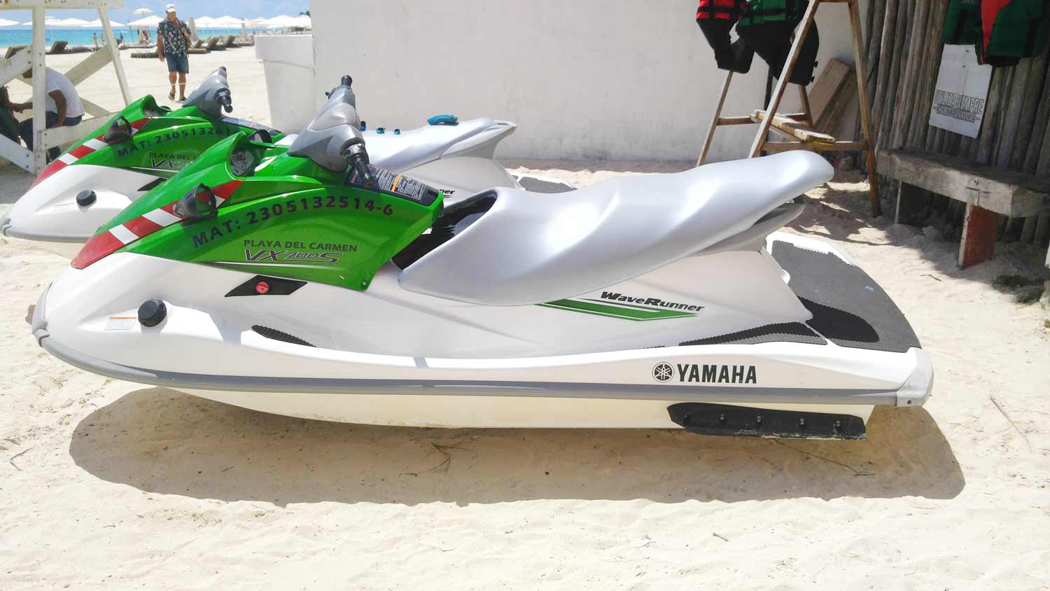 A side view of two green and white jet skis on the beach near the ferry dock in Playa Del Carmen.
