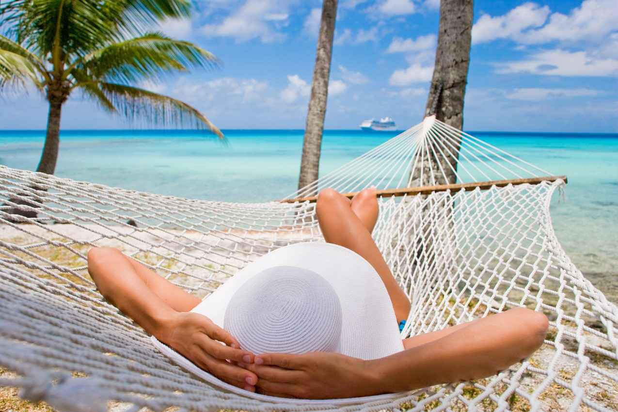 A woman comfortably lying in a hammock looking out at the Caribbean Sea.
