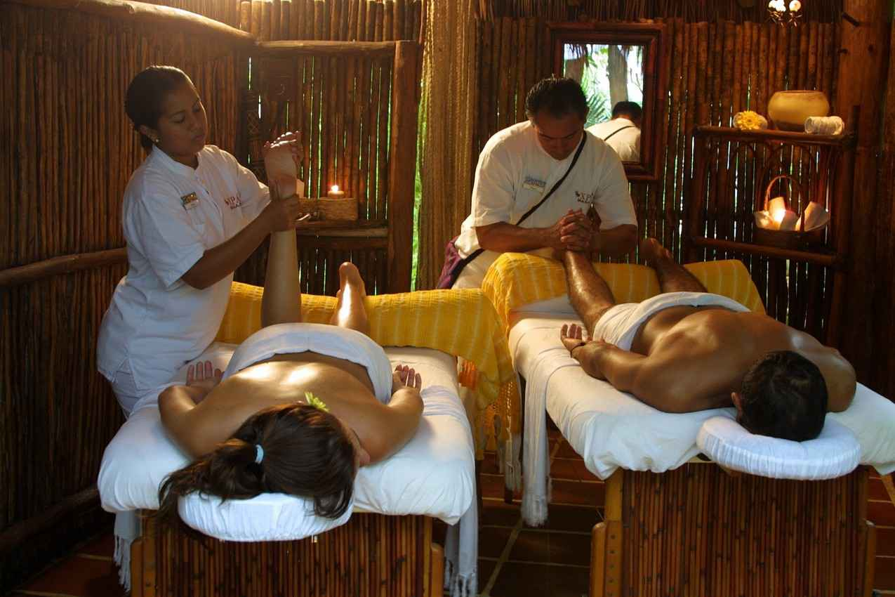 A man and a woman receiving massages at the same time.