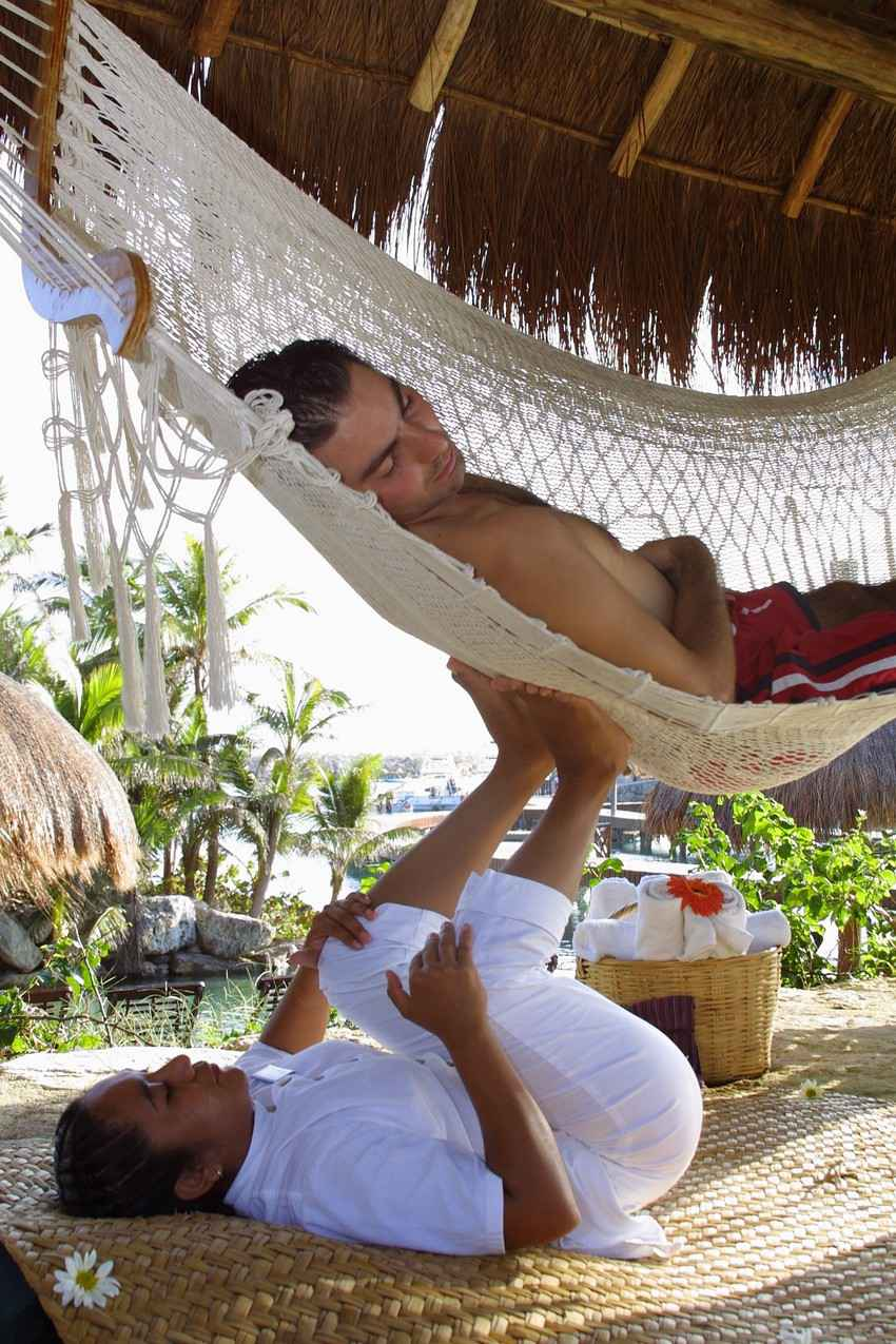 A man receiving a special foot massage in a hammock near Playa Del Carmen.