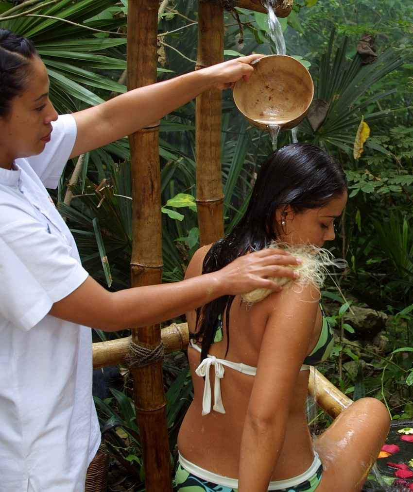 A woman pouring water over another woman's head during a special massage and cleansing procedure.