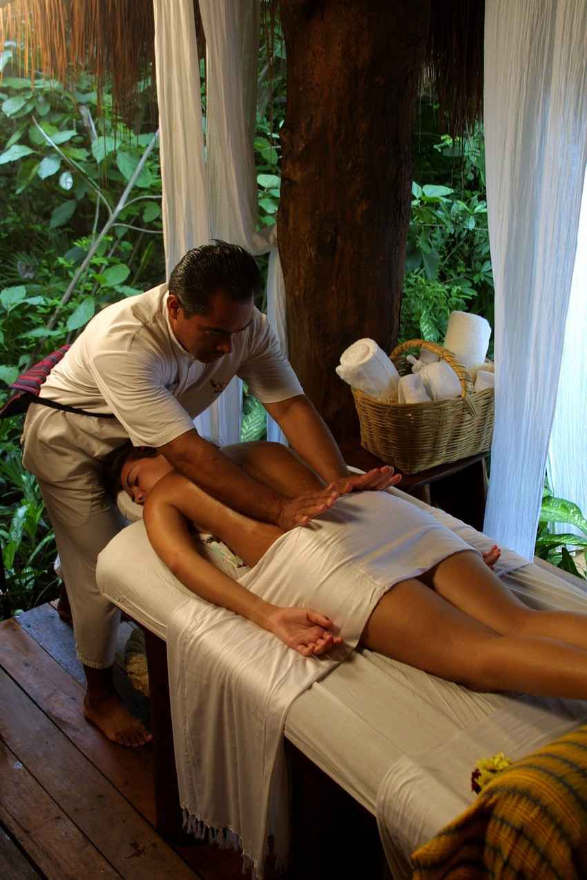 A woman receiving a hand massage in a jungle-style setting.