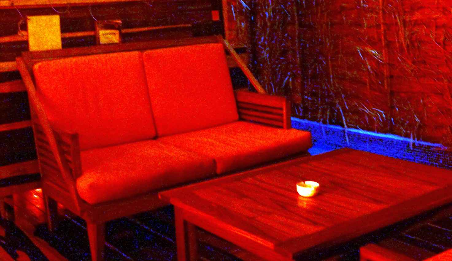 A dimly lit red room in a local Playa Del Carmen bar.