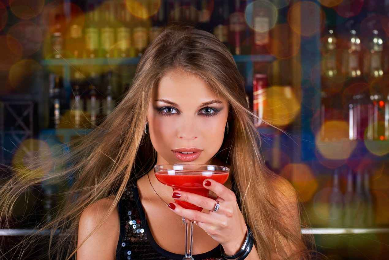A super hot woman with nice makeup drinking a cocktail at a bar.