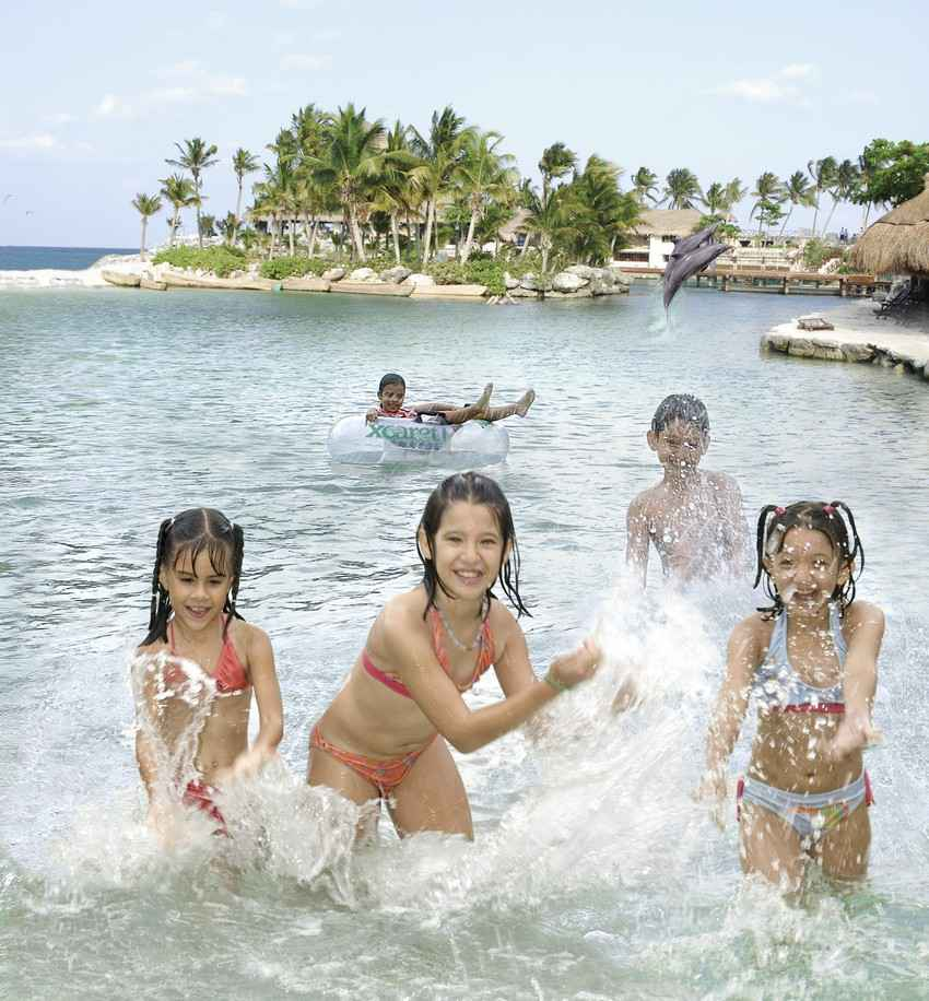Five children playing in the water at the Xcaret themepark.