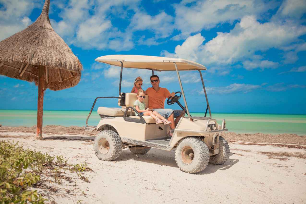 A man, woman, and son riding a golf cart on the beach.
