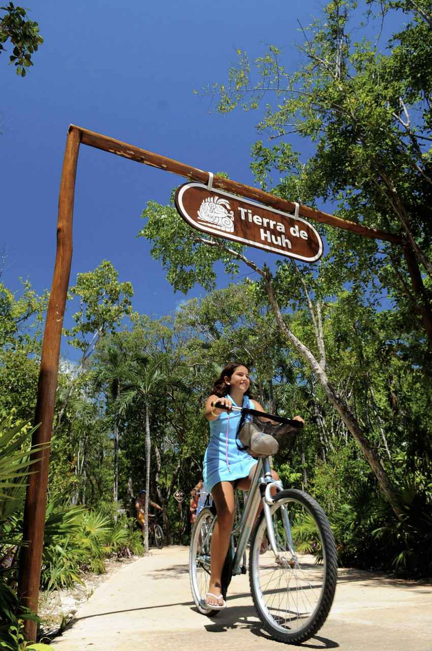 A young girl riding a bicycle during a jungle bike tour at a theme park near Playa Del Carmen.