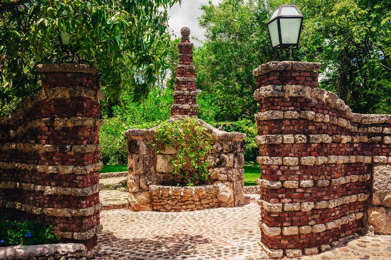 A beautiful brick entrance featuring a water fountain on some expensive property.