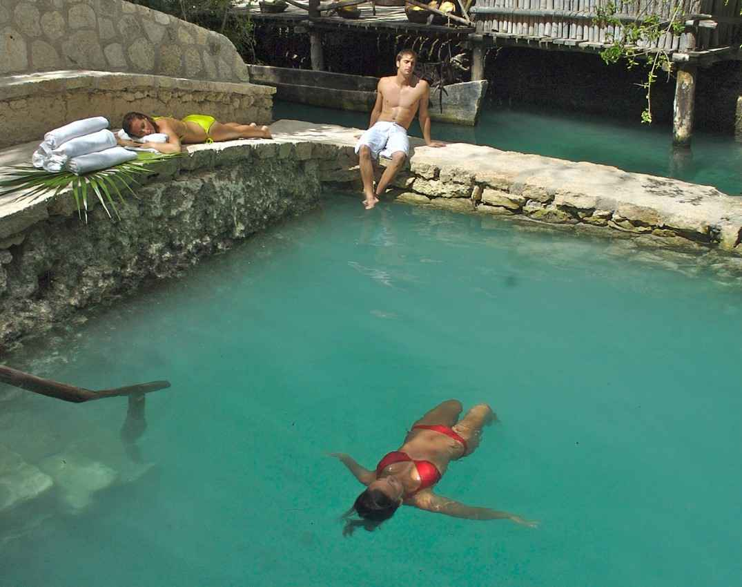 A man and two women swimming in a pool.