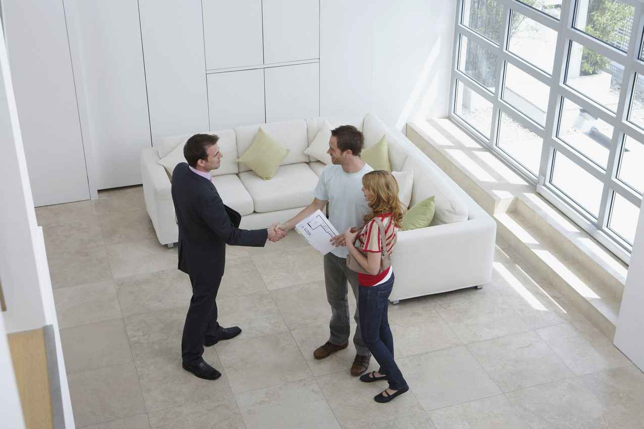 A man and a woman shaking hands with a realtor in a beautiful Playa Del Carmen home.
