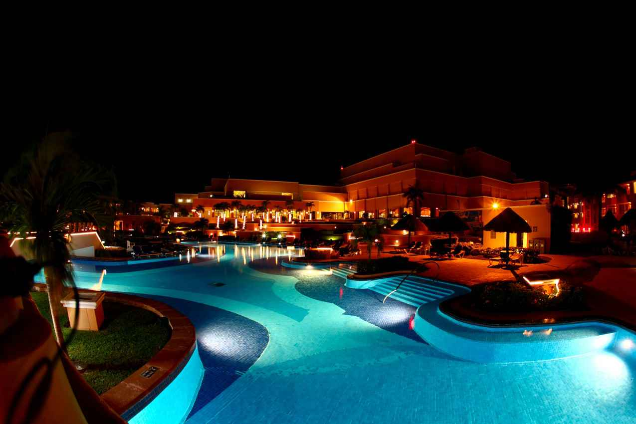A beautiful and brightly lit resort swimming pool at night.