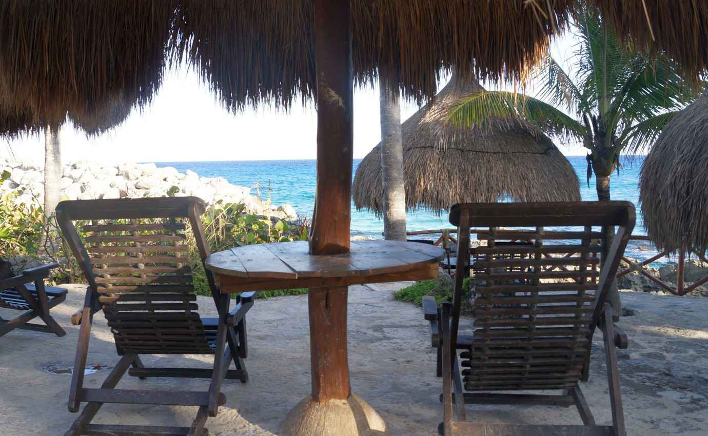Two lounge chairs facing the beach and the Caribbean Sea.