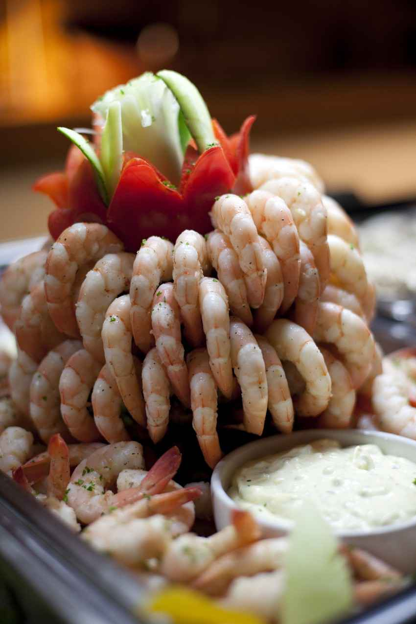 A shrimp cocktail dish with delicately cut vegetables and dip.