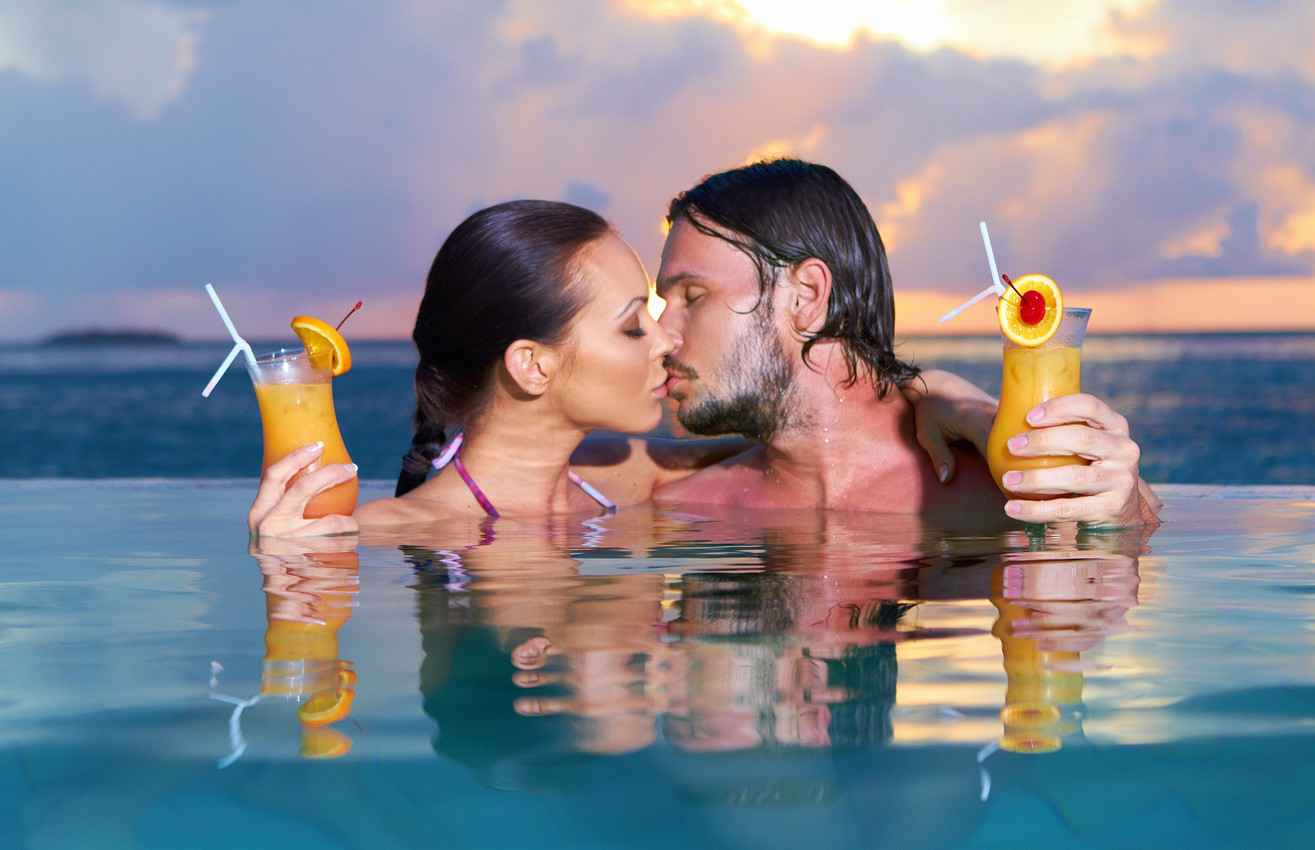 A man and a woman making out in a beachside pool.