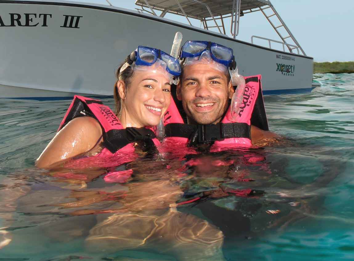 A man and woman are snorkeling near Playa Del Carmen at Xcaret theme park.