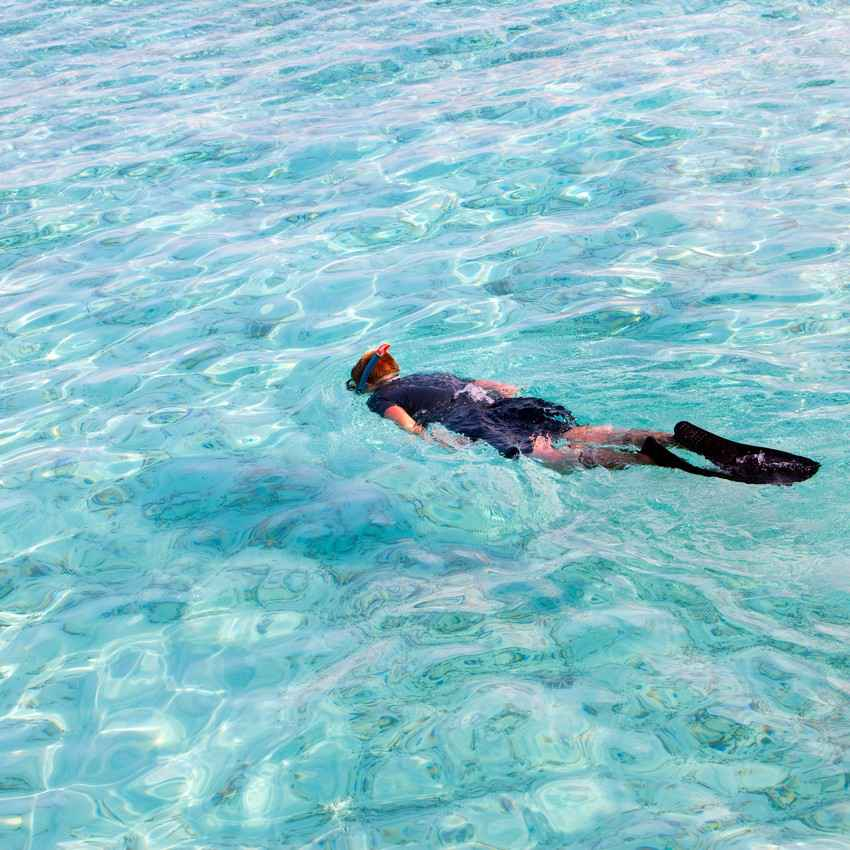 Another woman is snorkeling in crystal blue clear water near Playa Del Carmen.