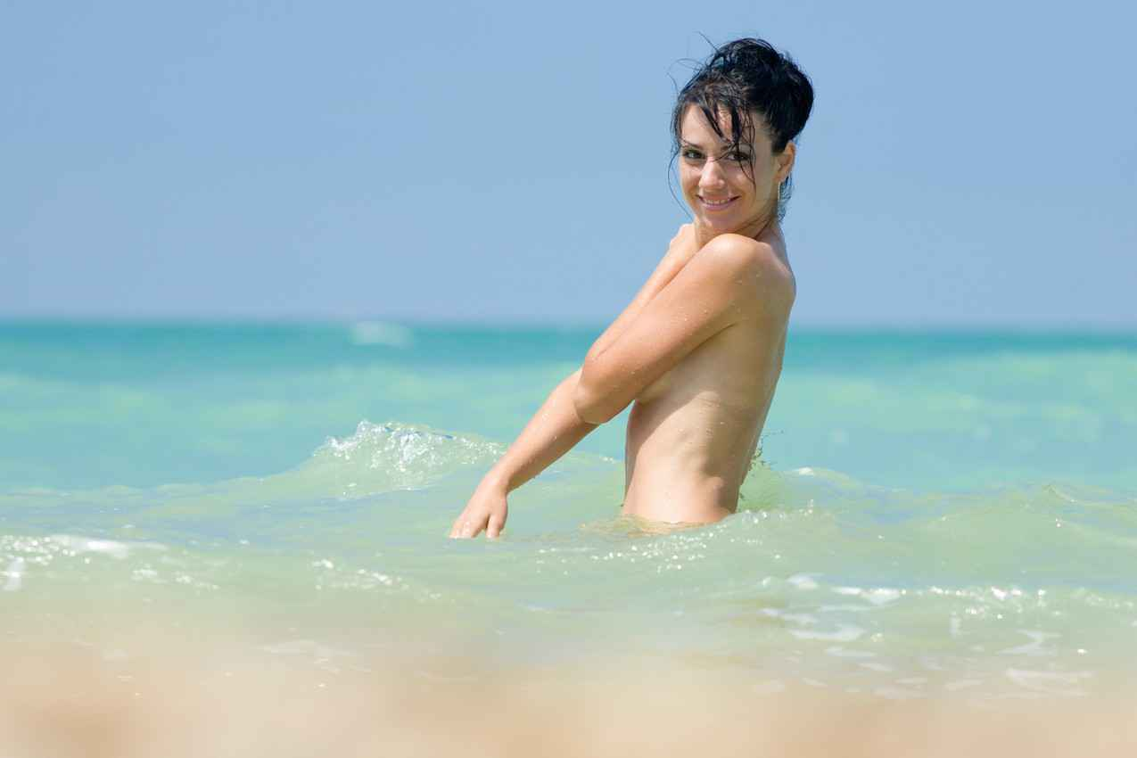 A topless woman in Playa Del Carmen swimming in the ocean.
