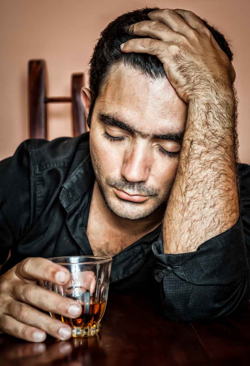 A drunk hairy man falling asleep at a bar with a whiskey glass in his hand.