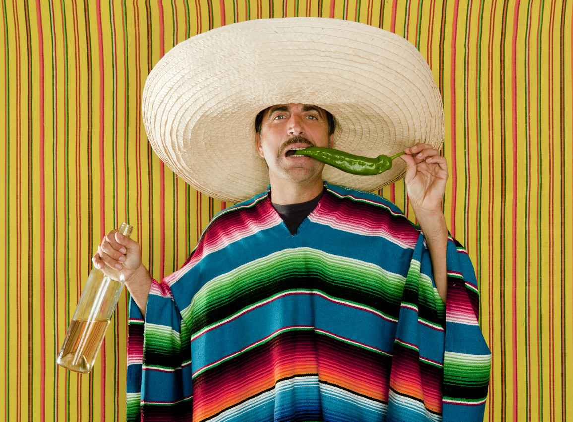 A drunk Mexican man wearing a sombrero and drinking tequila while eating a chili.