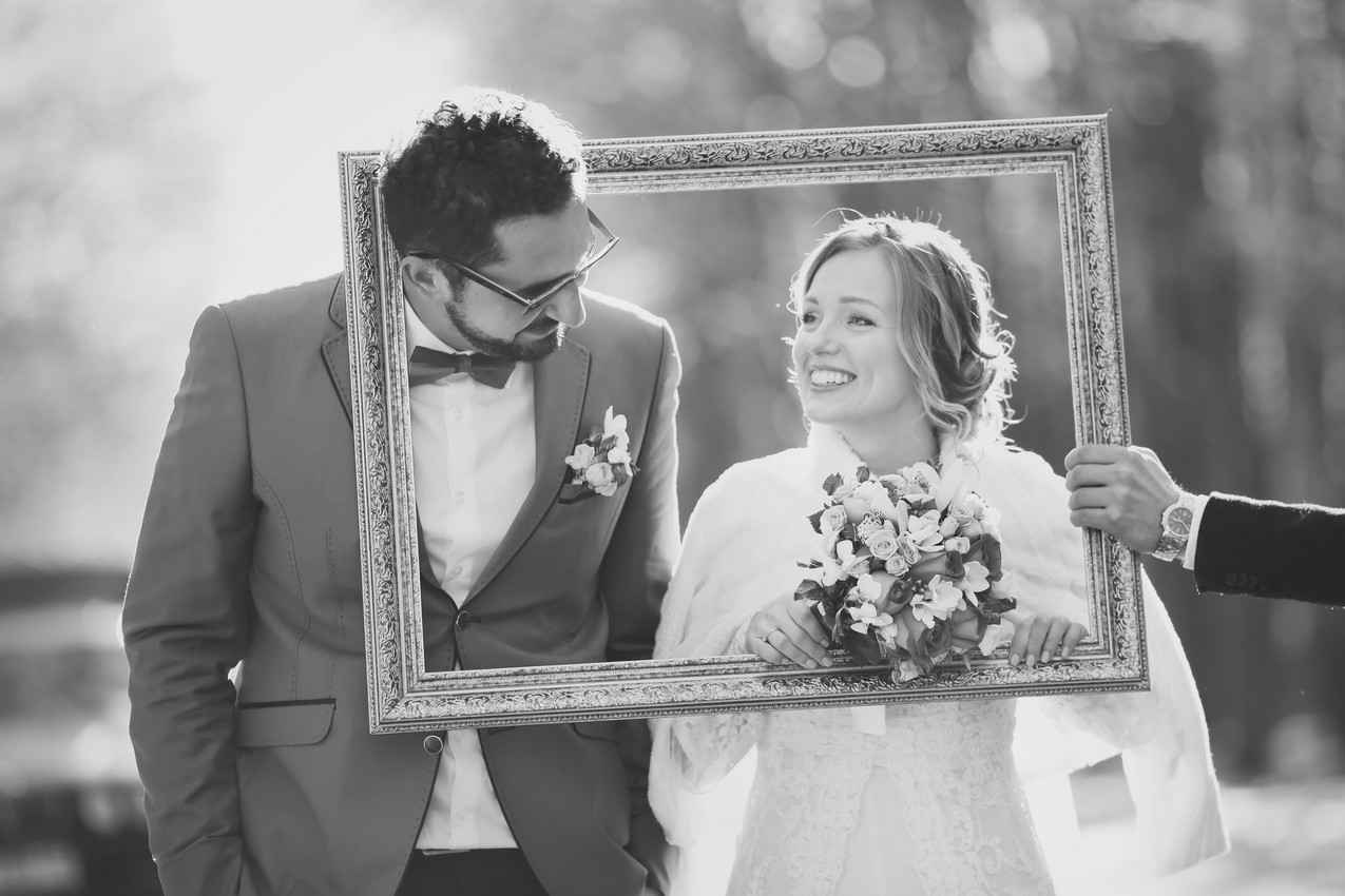A black-and-white photograph of a bride and groom in a picture frame.