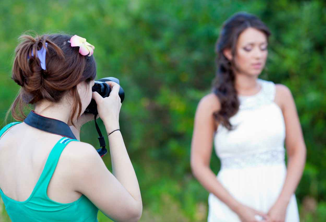 A female wedding photographer taking beautiful pictures of a bride with a jungle in the background.