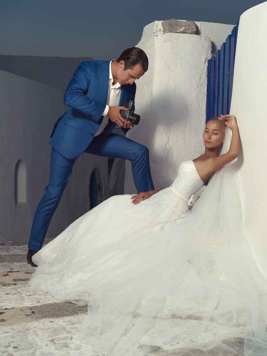 A photographer taking an exotic photo of a bride in a photography studio.