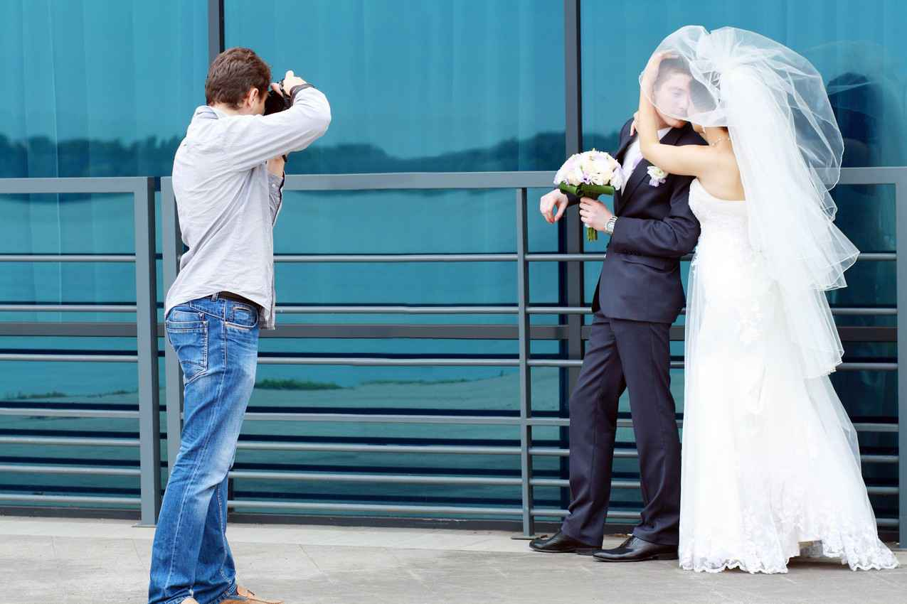A photographer taking pictures of a bride and groom in Cancun.