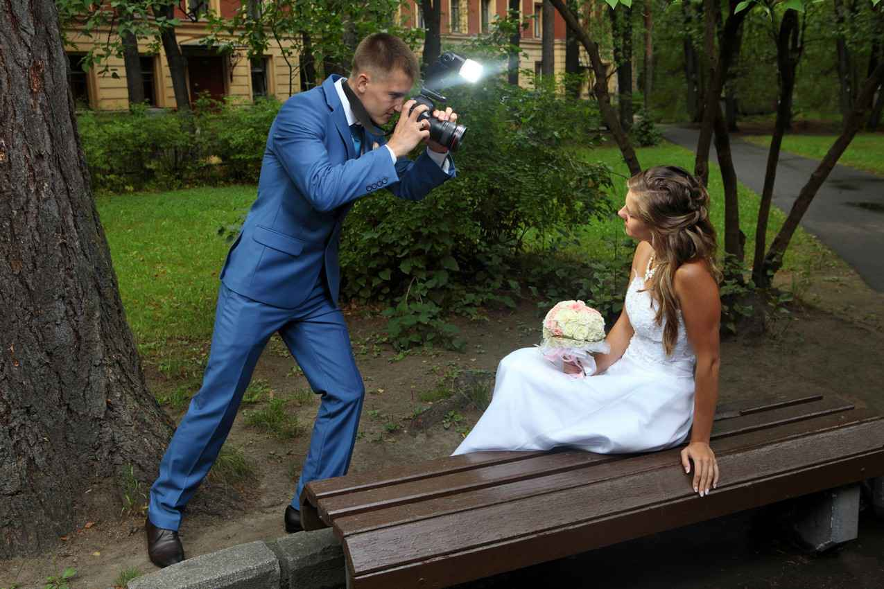 A photographer taking pictures of a bride with a bright flash.