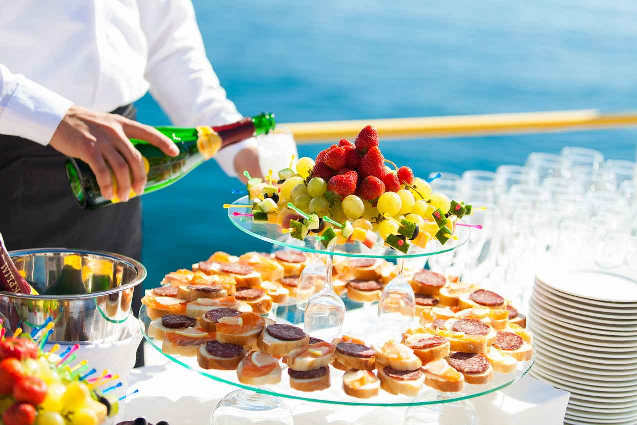 A waiter serving fruit and champagne at a wedding reception.