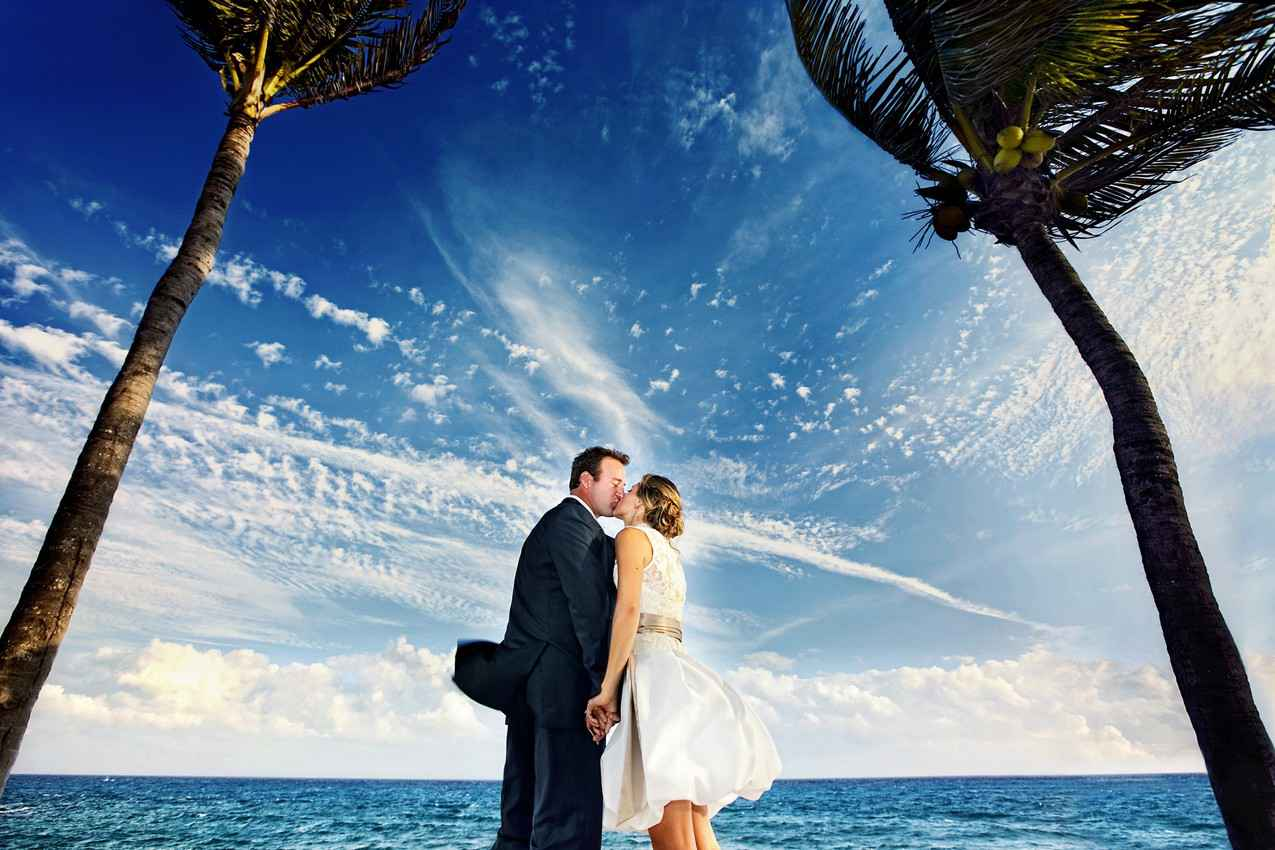 A bride and a groom on the beach with the sea on one side and palm trees on the other side.