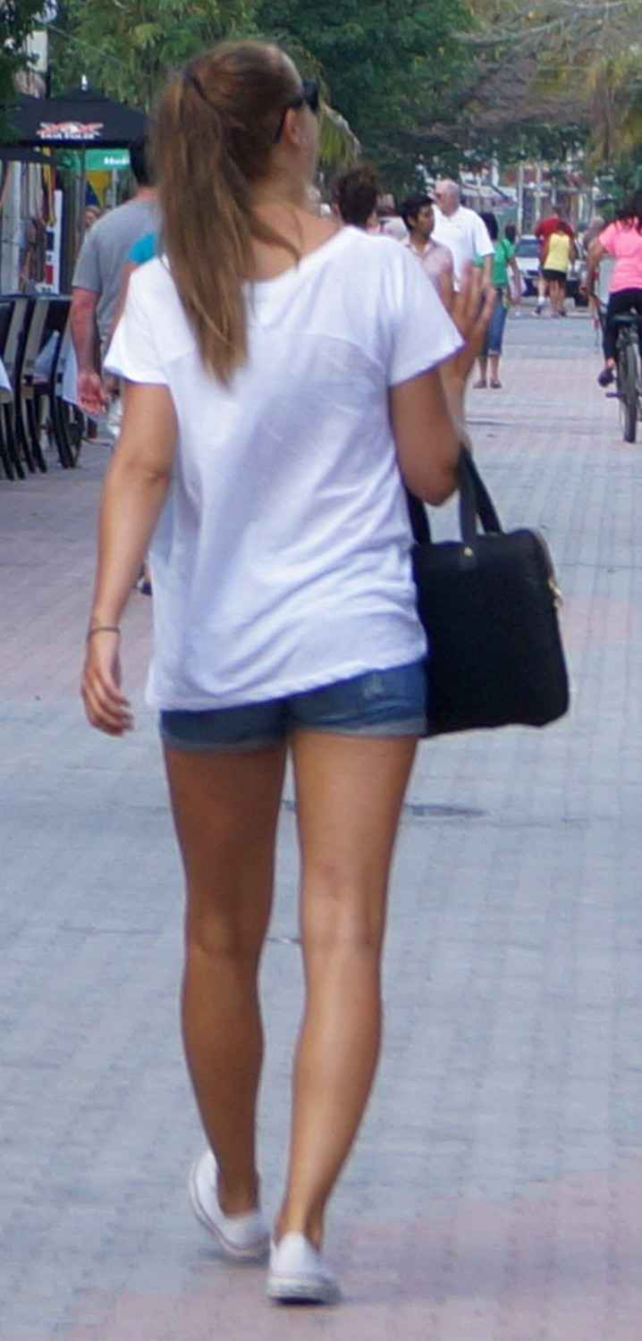 A very hot woman walking down Fifth Avenue in Playa Del Carmen.