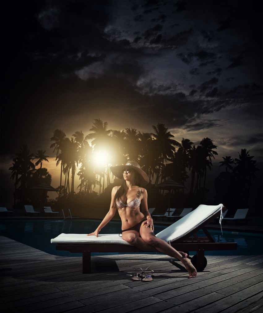 A sexy brunette sitting on a lounge chair in front of a pool with the sunset in the background.