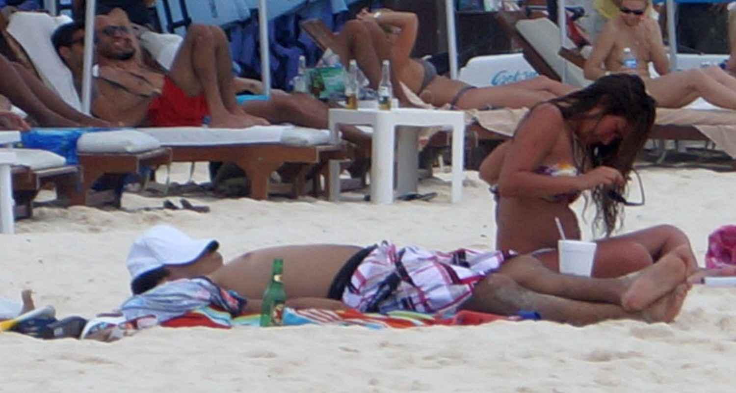 A tanned woman adjusting her bikini top at a beach in Playa Del Carmen.