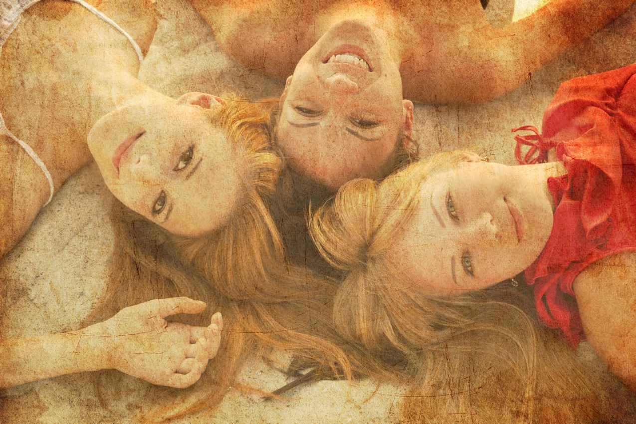 Three super hot strawberry blonde women laying on the beach.