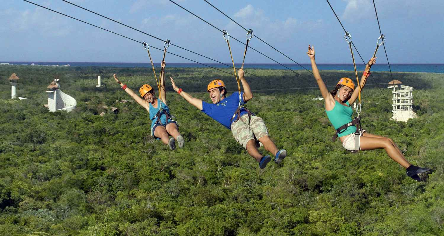 Three people hanging high above the jungle on a zip line.