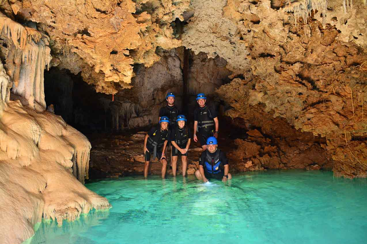 4-tourists-with-guide-standing-in-rio-secreto-cancun-cave-near-crystal-clear-water